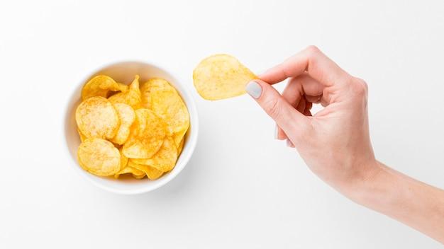 Рука с картофельными чипсами Premium Фотографии