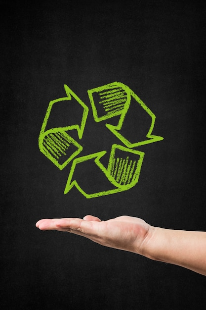 Hand with a recycling symbol drawn on a blackboard Free Photo