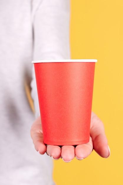 Рука с красной одноразовой чашкой изолирована Premium Фотографии