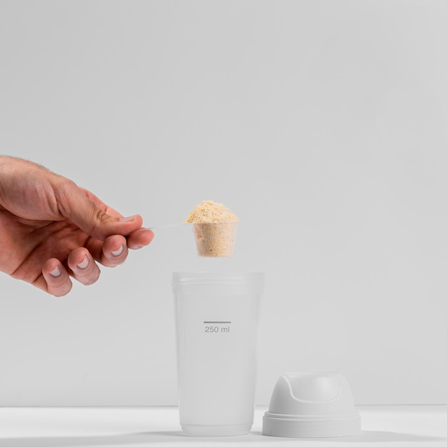 Hand with scoop of gym supplements Free Photo