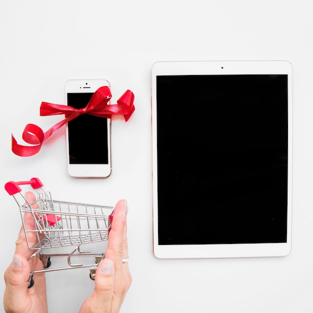 Hand with shopping trolley near tablet and smartphone Free Photo