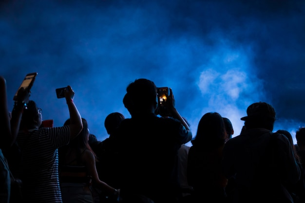 Hand with a smartphone records live music festival, taking photo of concert stage Premium Photo