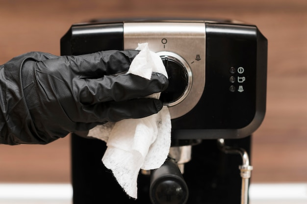 Hand with surgical glove disinfecting espresso machine Premium Photo