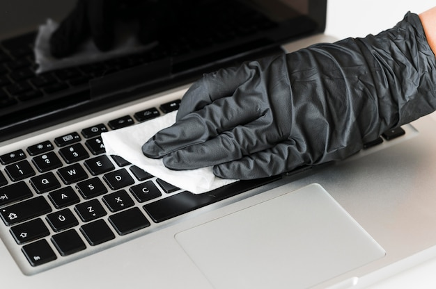 Hand with surgical glove disinfecting laptop surface Premium Photo