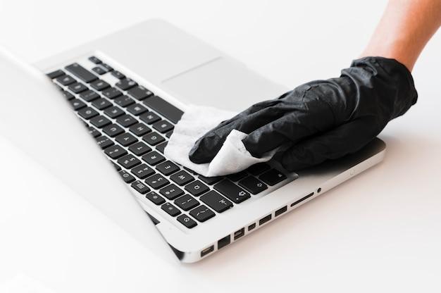 ラップトップを消毒する手術用手袋を持った手 Premium写真