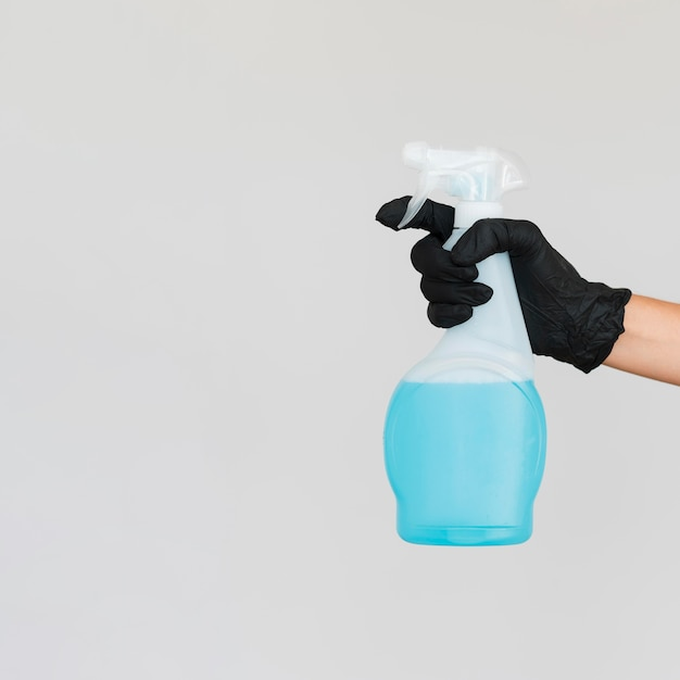 Hand with surgical glove holding cleaning solution bottle with copy space Premium Photo