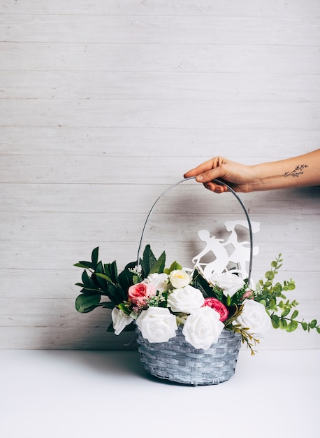 Hand With Tattoo Holding Fresh Flower Basket On White Desk Against