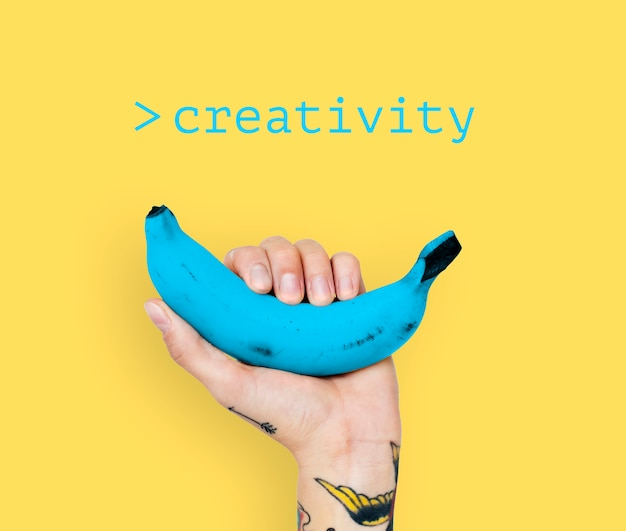 Hand with tattoo lifting blue banana with yellow background Free Photo