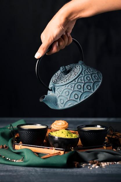 Рука с чайником наливая напиток в чашке Бесплатные Фотографии