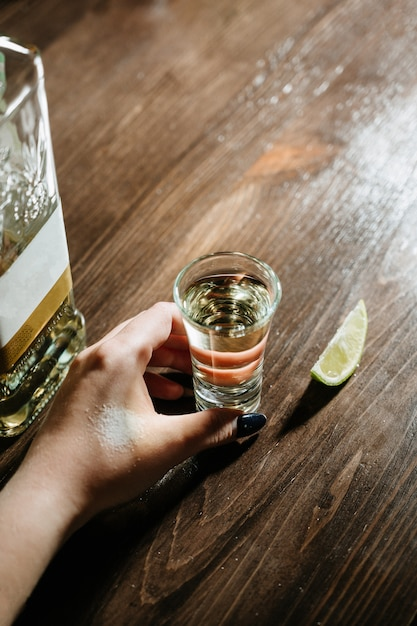 Hand with tequila shots on wooden tabletop Premium Photo