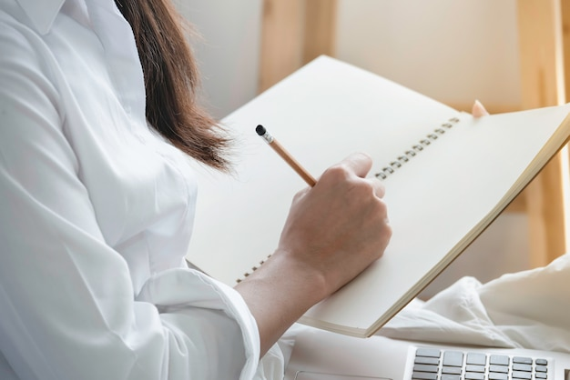 Hand  of woman in casual clothes holding pencil writing empty notebook. Premium Photo