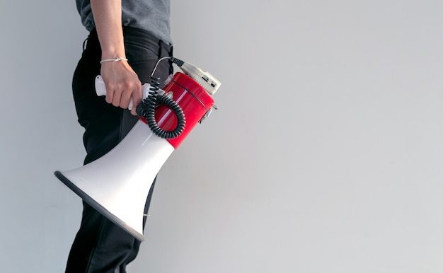 Hand of woman holding megaphone on white brick wall background Premium Photo