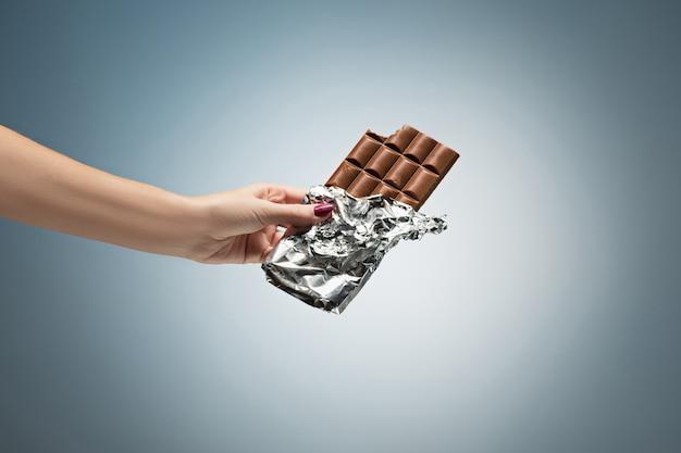 Mano di una donna che tiene una piastrella di cioccolato Foto Gratuite