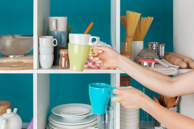 Hand of a woman taking kitchenware from a kitchen shelf Premium Photo