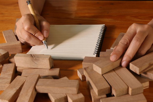 Hand of woman writing on note book and holding wooden block Premium Photo
