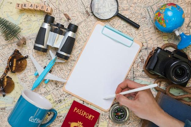 Hand writing on folder surrounded by travel elements Free Photo