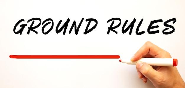 빨간색 표시와 함께 지상 규칙을 작성하는 손. 흰색 배경에 고립. 비즈니스 개념. 프리미엄 사진