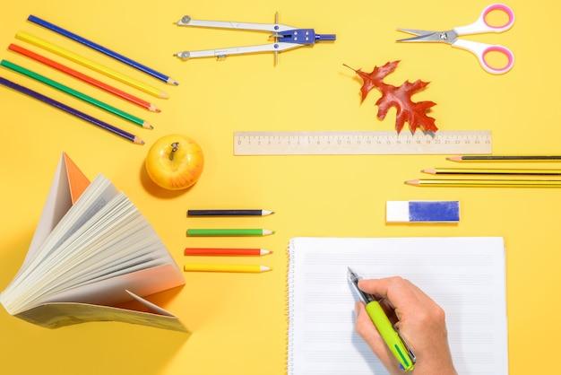 Почерк в блокноте на столе со школьными принадлежностями Premium Фотографии