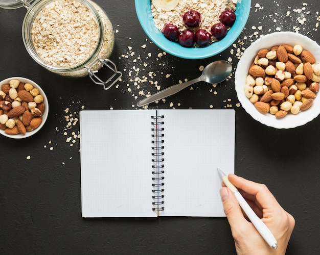 Hand writing on notebook near nuts mix and oats jar Free Photo
