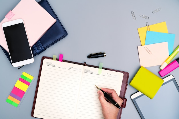 Hand writing on notebook surrounded with office accessories. Premium Photo