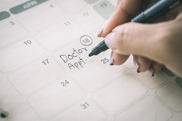 Рукописный написание напоминание о назначении врача в календаре Premium Фотографии