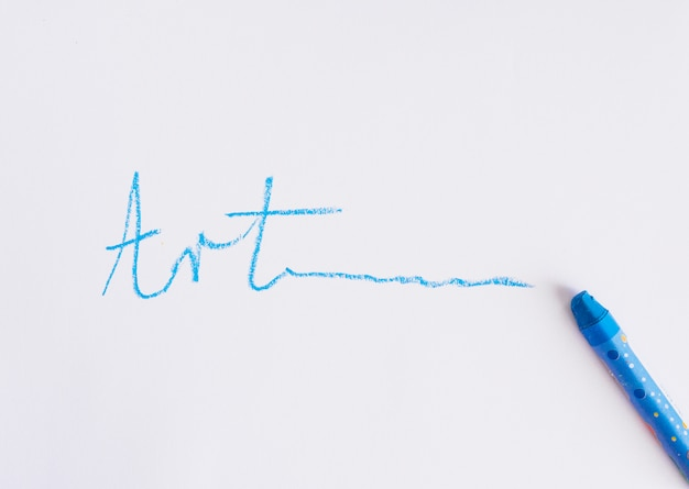 Hand written art text near blue crayon on a white background Free Photo