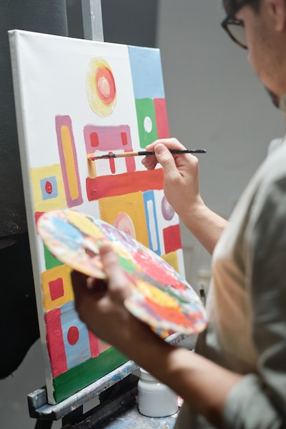 Hand of young artist holding color palette while using paintbrush during work over new painting on canvas in studio of arts Premium Photo