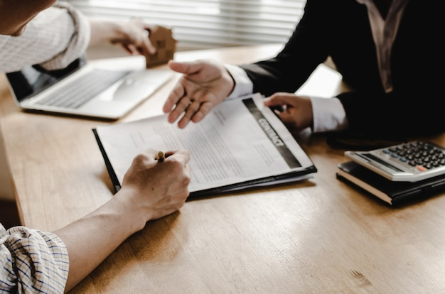 Hand of young man customer signing contract for buying house with real estate broker Premium Photo