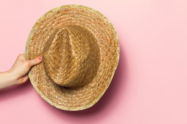 Hand of young woman holding summer straw hat on pink background. fashion background. summer concept. Free Photo