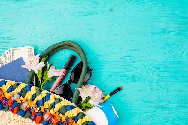 Handbag with money among flowers near sunglasses and lipstick Free Photo