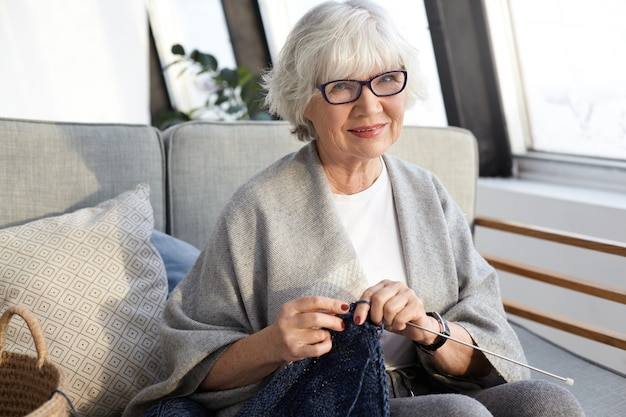 Handcraft, hobby, age and retirement concept. elegant beautiful elderly female with wrinkles and short gray hair enjoying leisure time, sitting in living room and knitting stylish scarf for herself Free Photo