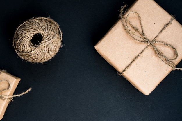 Handcrafted gift box wrapped in craft paper with rope and bow. top view, flat lay Premium Photo