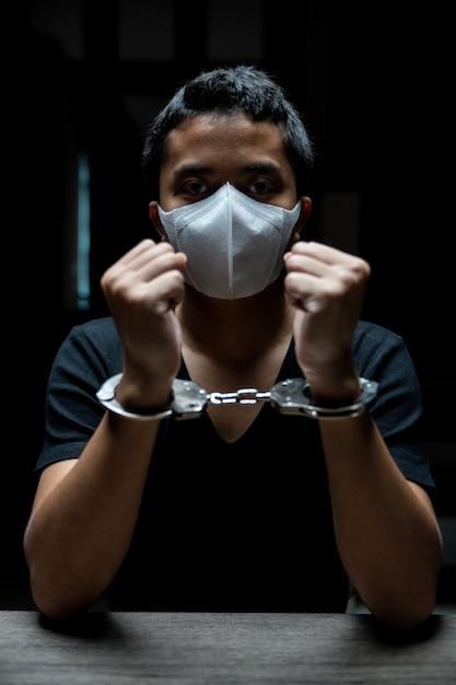 Handcuffed on a prisoner, male prisoners were handcuff in the dark prison. Premium Photo