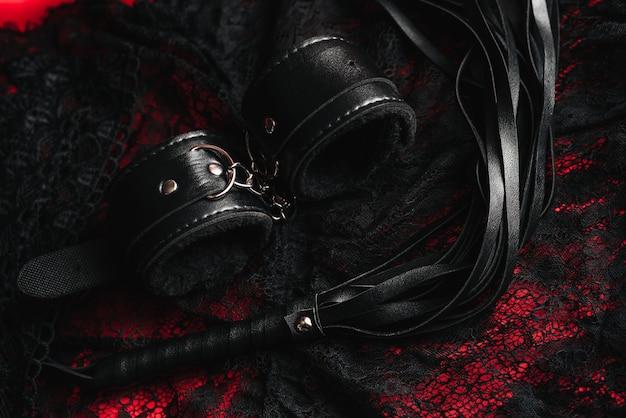 Handcuffs and a whip with women sexy underwear Premium Photo