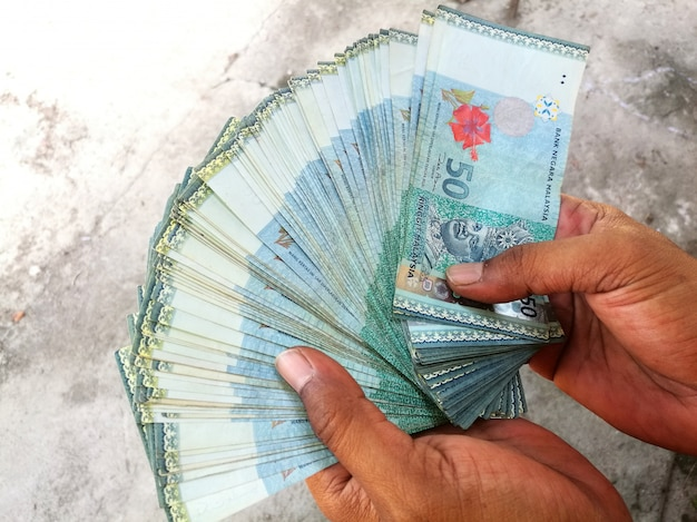 Handful of malaysian ringgit banknotes showing outdoor on gray textured background Premium Photo