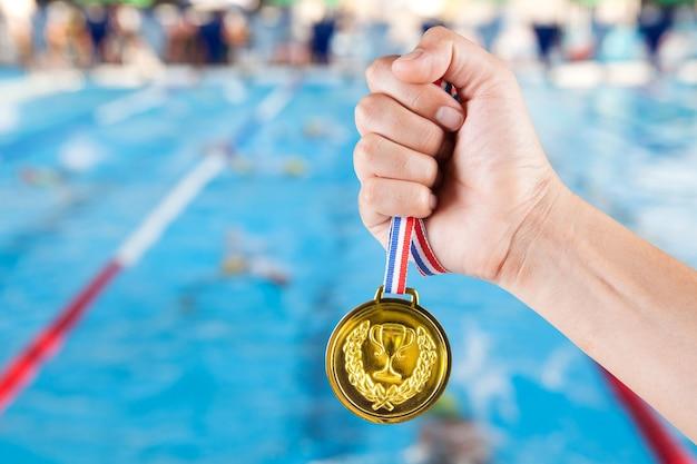 スイミングプールと水泳競争のぼやけた背景で金メダルを保持する少数のアジア人。 Premium写真