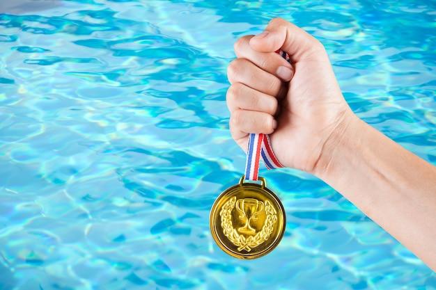 スイミングプールのぼやけた背景で金メダルを保持しているアジア人の一握り。 Premium写真