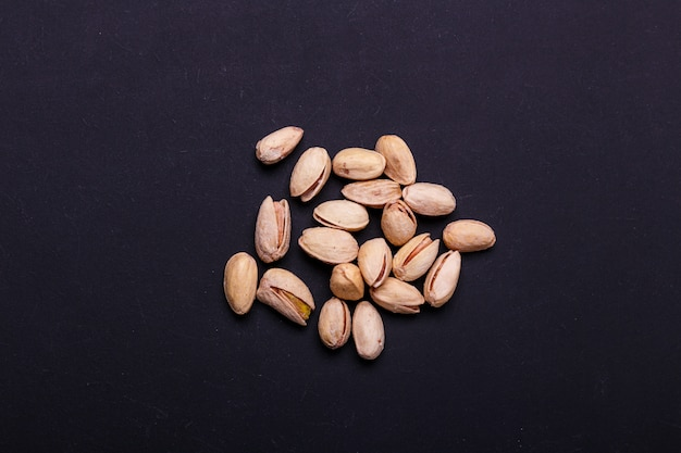 Handful of pistachios on a black slate - healthy snack. Premium Photo