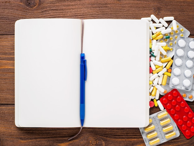 Handful of scattered medicines, pills and tablets and note pad on