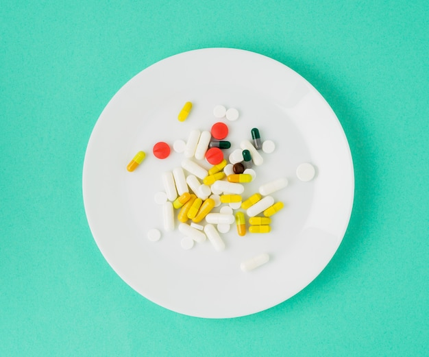 Handful of scattered medicines, pills and tablets on white plate on