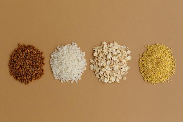 갈색 바탕에 다양 한 곡물의 소수입니다. 쌀과 오트밀, 메밀과 기장 프리미엄 사진