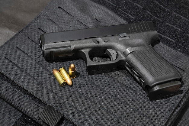 Handgun and 9mm bullets on a bulletproof jacket Premium Photo