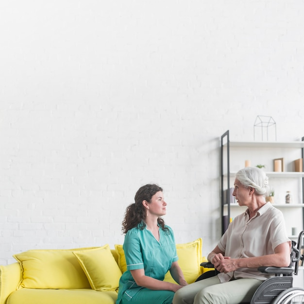 Handicapped senior woman sitting on wheel chair looking at nurse Free Photo