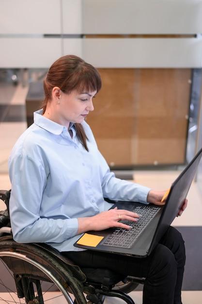 ノートパソコンを見てオフィスで障害を持つ若い女性 無料写真