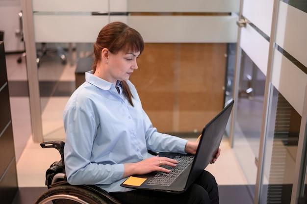 ラップトップに取り組んでいるオフィスで障害を持つ若い女性 無料写真