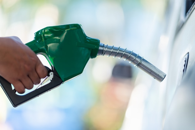 Handle pumping gasoline fuel nozzle to refuel. vehicle fueling facility at petrol station. white car at gas station being filled with fuel. transportation and ownership concept. Premium Photo