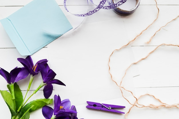 Handmade artificial purple flowers; paper; ribbon; clothespin and string on white plank backdrop Free Photo
