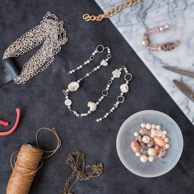 Handmade beads with spool yarn and beads on textured backdrop Premium Photo