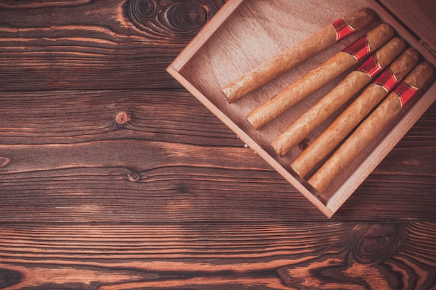 Handmade cigars on a wooden background with copyspace Premium Photo