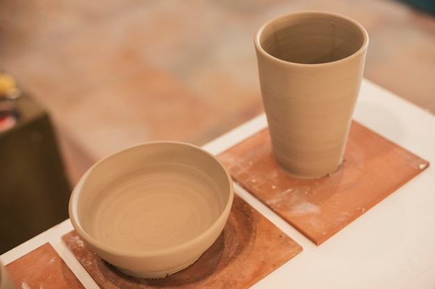 Handmade clay bowl and glass on table Free Photo